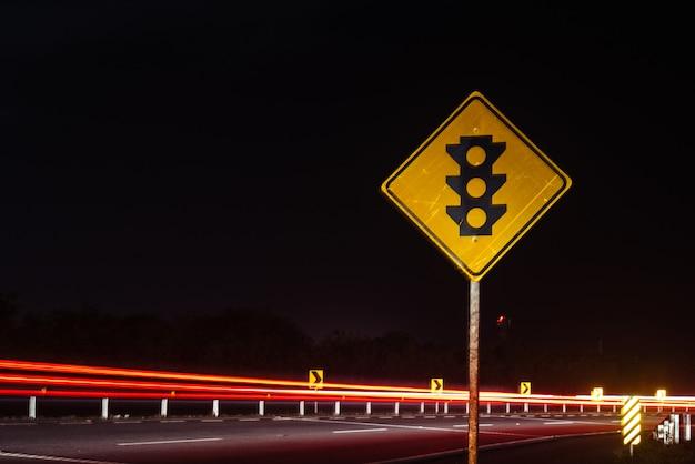 Um sinal de trânsito do semáforo no meio do caminho alto