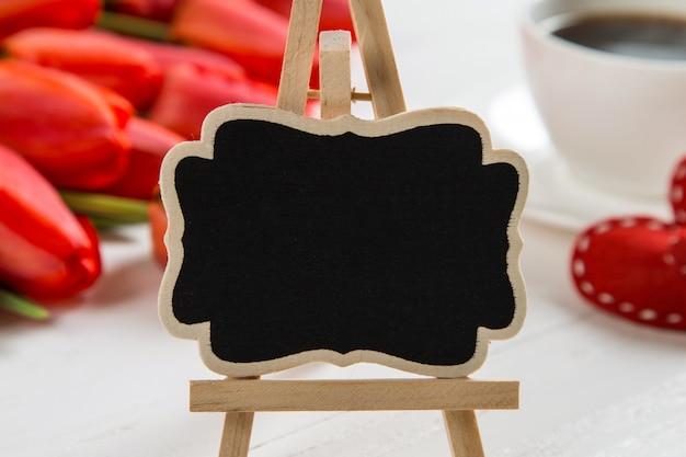 Um sinal preto contra tulipas vermelhas, corações e xícaras de café na mesa branca.