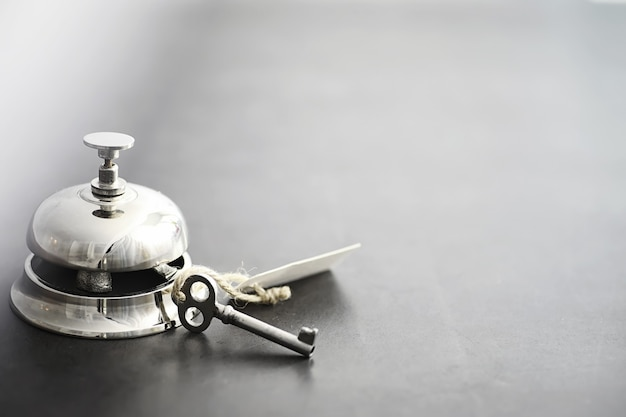 Um sino de metal prateado brilhante na recepção do hotel. uma mesa no hotel na portaria com campainha e chave da porta. chave e campainha em um hotel.