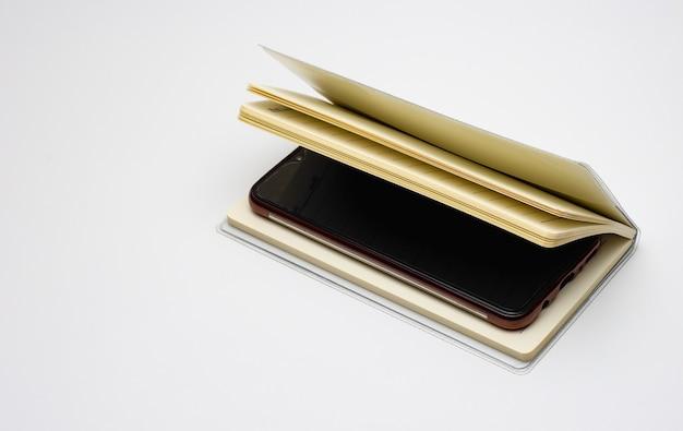 Um smartphone dentro de um diário aberto com espaço de cópia em branco