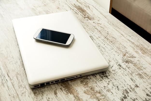 Um smartphone e um laptop desligado em uma área de trabalho de madeira.