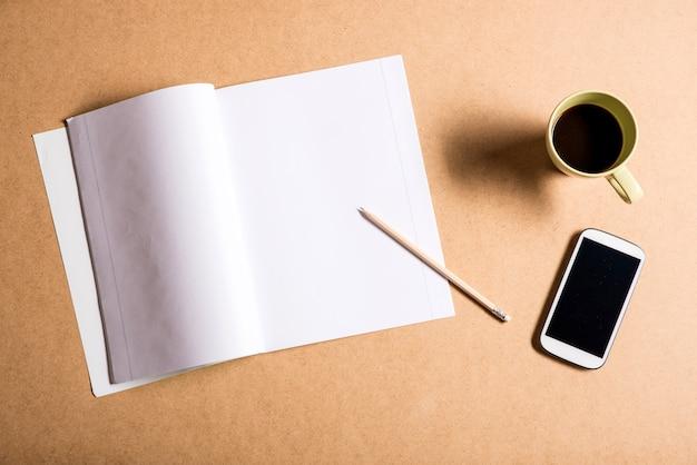 Um smartphone e um livro de exercícios sobre uma mesa de madeira.