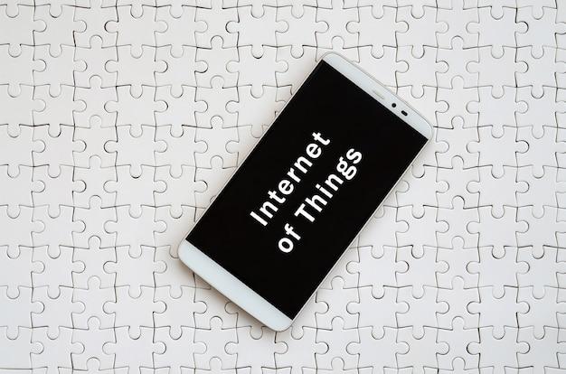 Um smartphone grande moderno com uma tela de toque encontra-se em um enigma de serra de vaivém branco em um estado montado com inscrição. internet das coisas