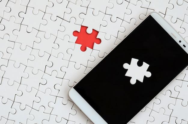 Um smartphone grande moderno com vários elementos de quebra-cabeça na tela de toque encontra-se em um quebra-cabeça branco