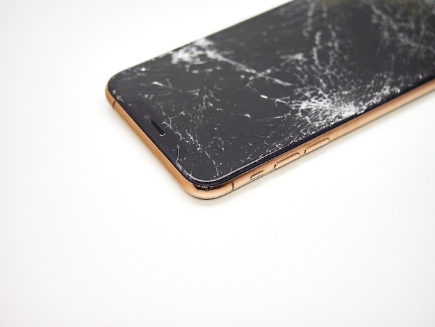 Um smartphone moderno dourado com uma tela de vidro quebrado e um close-up do corpo curvo danificado isolado na superfície branca