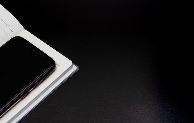 Um smartphone preto acima de um caderno aberto em um fundo escuro e áspero com espaço de cópia