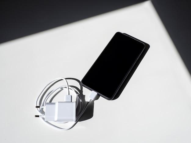 Um smartphone preto com um fio de carregamento em uma mesa branca com sombras. vista do topo.
