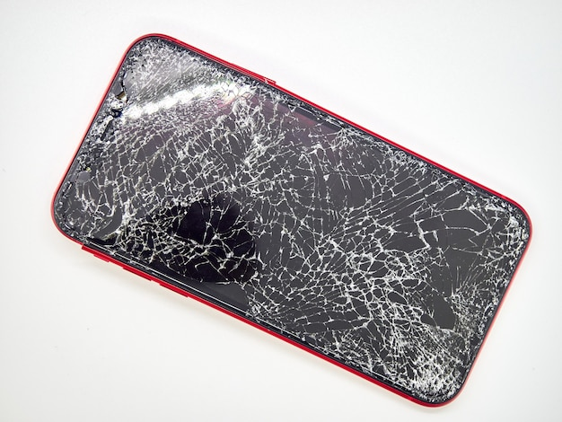 Um smartphone vermelho moderno com uma tela de vidro quebrado e um close-up do corpo curvo danificado isolado na superfície branca