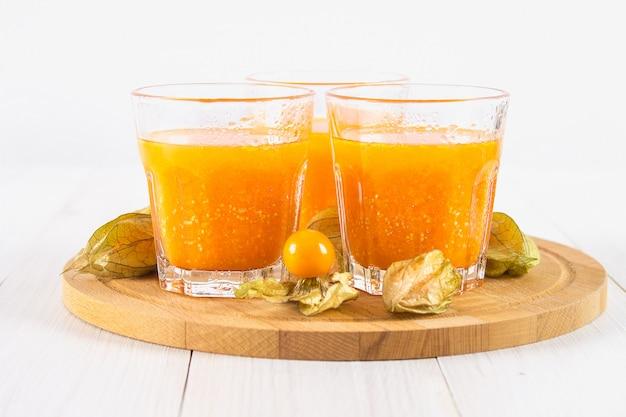 Um smoothie de laranja feito de physalis em uma mesa de madeira branca.