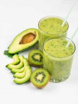 Um smoothie preparado na hora de abacate, banana, laranja, limão e kiwi em uma mesa branca. faça dieta comida vegetariana. alimentos crus.
