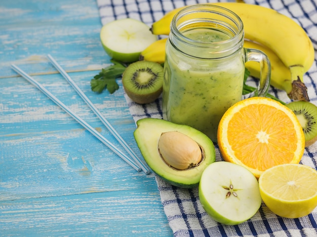 Um smoothie preparado na hora de abacate, banana, laranja, limão e kiwi em uma mesa de madeira azul. faça dieta comida vegetariana. alimentos crus.