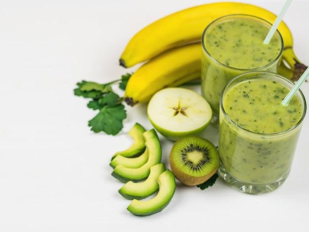 Um smoothie preparado na hora de abacate, banana, laranja, limão e kiwi em uma mesa de madeira branca. faça dieta comida vegetariana. alimentos crus.