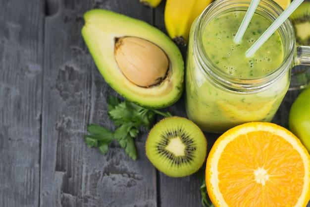 Um smoothie preparado na hora de abacate, banana, laranja, limão e kiwi em uma mesa de madeira escura. faça dieta comida vegetariana.