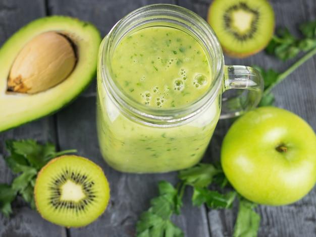 Um smoothie preparado na hora de abacate, banana, laranja, limão e kiwi em uma mesa de madeira. faça dieta comida vegetariana. vista do topo.