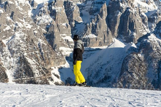 Um snowboarder em uma jaqueta preta e calça amarela fica em uma pista de esqui contra o pano de fundo da montanha.