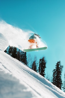 Um snowboarder salta de um trampolim alto coberto de neve em uma floresta contra um céu azul. esportes extremos