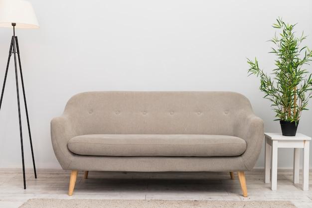 Um sofá confortável vazio na sala de estar perto do vaso de plantas no banco