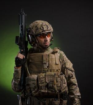 Um soldado com roupas militares e uma arma em um fundo escuro