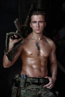 Um soldado forte e atraente com um torso musculoso em um uniforme de camuflagem