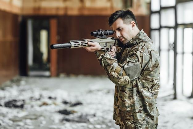 Um soldado militar tem como alvo e segura um grande rifle no prédio