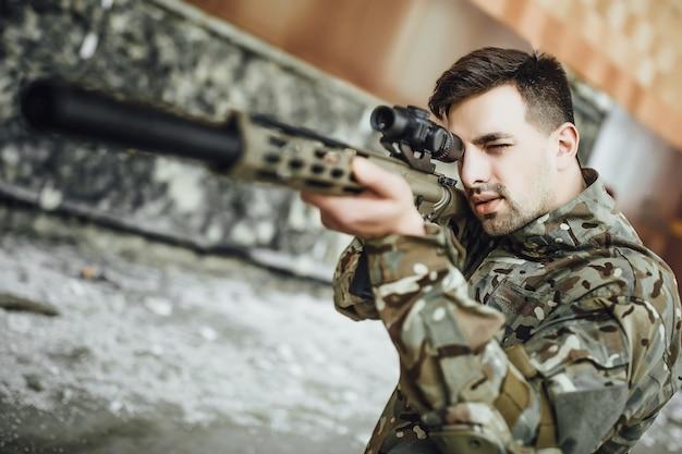 Um soldado militar tem como alvo e segura um grande rifle no prédio.