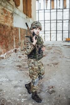 Um soldado uniformizado usa um grande rifle nas mãos