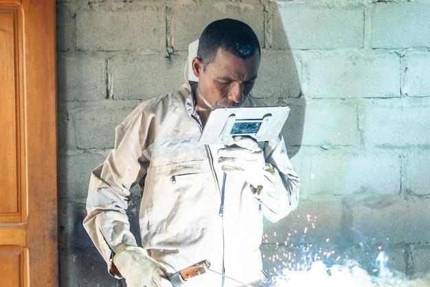 Um soldador latino solda durante um dia de trabalho na fábrica metalúrgica.