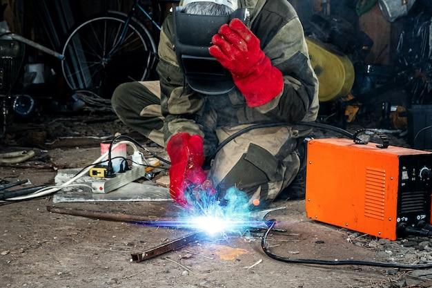 Um soldador masculino em uma máscara de solda trabalha com um eletrodo de arco em sua garagem. soldagem, construção, trabalhos em metal.
