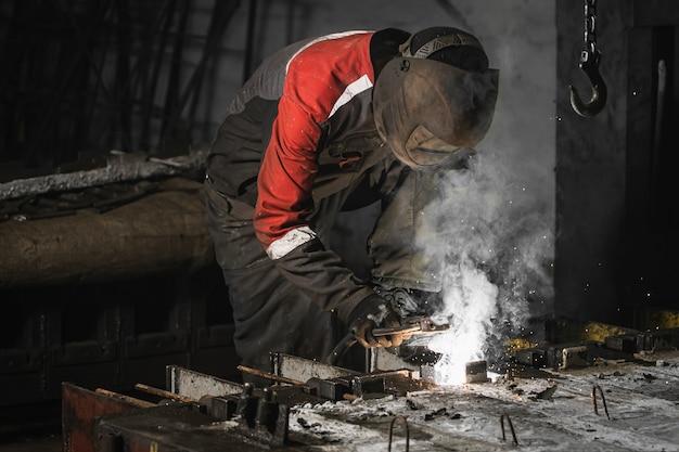 Um soldador masculino uniformizado trabalhando