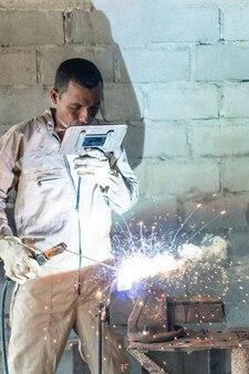 Um soldador solda durante um dia de trabalho na fábrica metalúrgica.