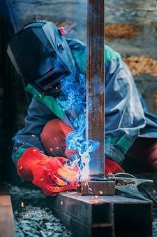 Um soldador solda um poste de metal com solda elétrica, segura um eletrodo nas mãos