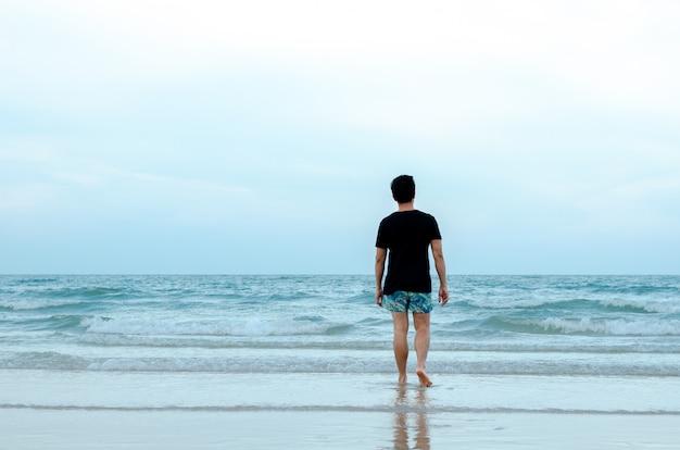 Um solitário homem asiático andando sozinho na praia