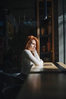 Um, solitário, mulher jovem, sentar perto, a, janela, com, telefone móvel, ligado, tabela