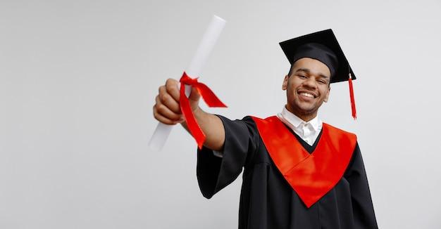 Um sorridente estudante negro em vestido de pós-graduação e boné quadrado que está feliz por terminar seus estudos mostra seu diploma há muito aguardado na graduação virtual e cerimônia de convocação classe de 2021