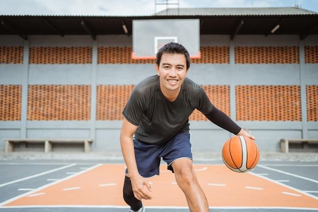 Um sorridente jogador de basquete fazendo um drible baixo entre as pernas e driblando a bola