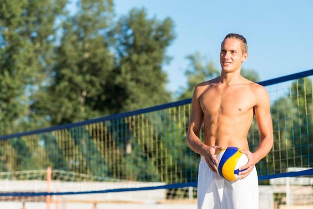 Um sorridente jogador de vôlei sem camisa na praia segurando uma bola