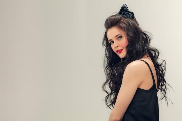 Um sorriso fofo. retrato de mulher jovem e bonita na parede cinza. modelo feminino moreno bonito caucasiano com cabelo longo cacheado. conceito de beleza, moda, cosméticos. copyspace para anúncio.