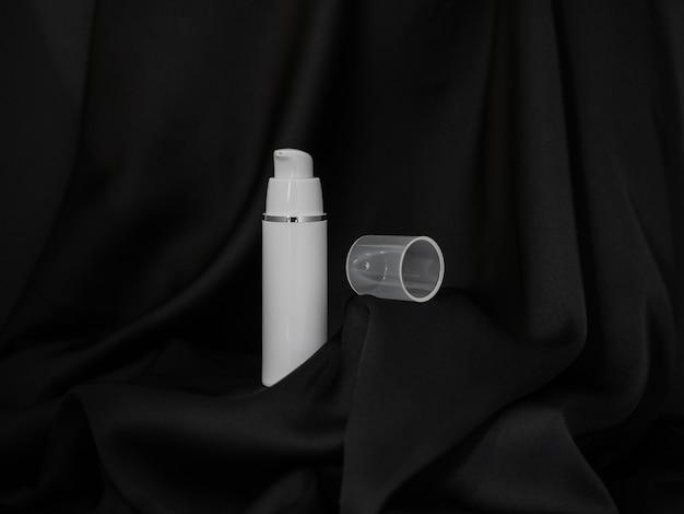 Um spray cosmético com uma tampa ao lado fica em um fundo de seda preta