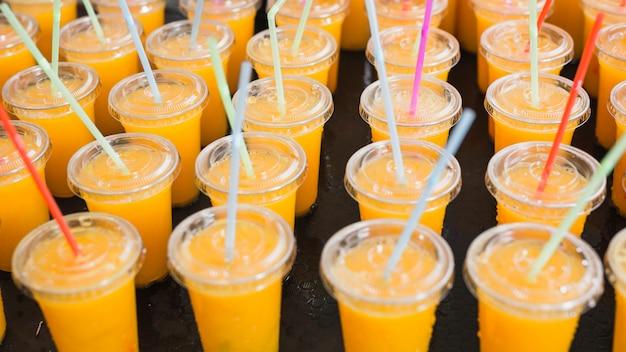 Um suco de laranja no copo descartável de plástico com canudos