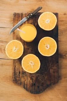 Um, suco laranja, com, metade, laranja, e, faca, ligado, tábua cortante, contra, madeira, fundo