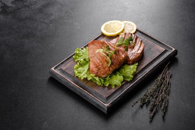 Um suculento bife de atum grelhado com especiarias e ervas e rodelas de limão