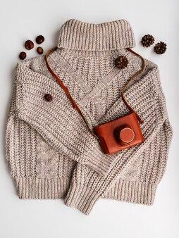Um suéter de lã quente e uma câmera velha em um estojo