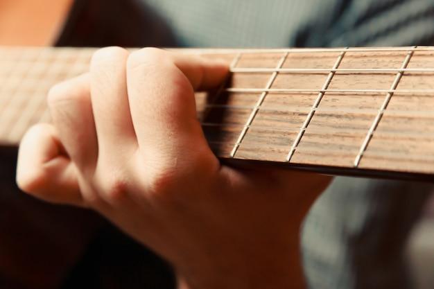 Um super close de uma mão tocando uma guitarra espanhola, musical de tiro conceitual