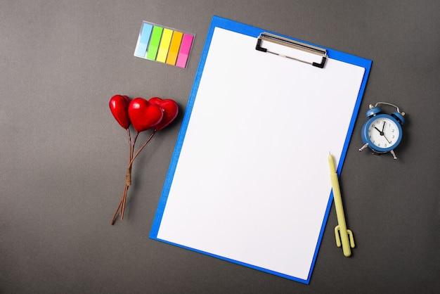 Um suporte de folha rodeado por algumas decorações e ferramentas para tornar o tempo mais produtivo e escrever o plano no papel