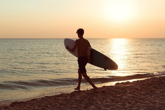 Um surfista ao pôr do sol.
