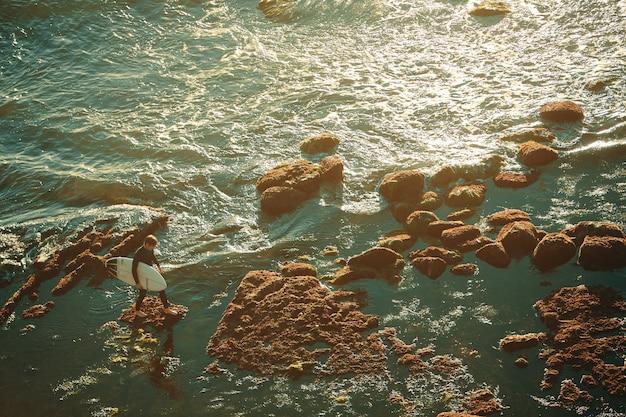 Um surfista masculino com prancha de surf em um recife de coral de um mar