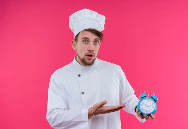 Um surpreendente jovem chef barbudo de uniforme branco mostrando um despertador azul enquanto olha para uma parede rosa