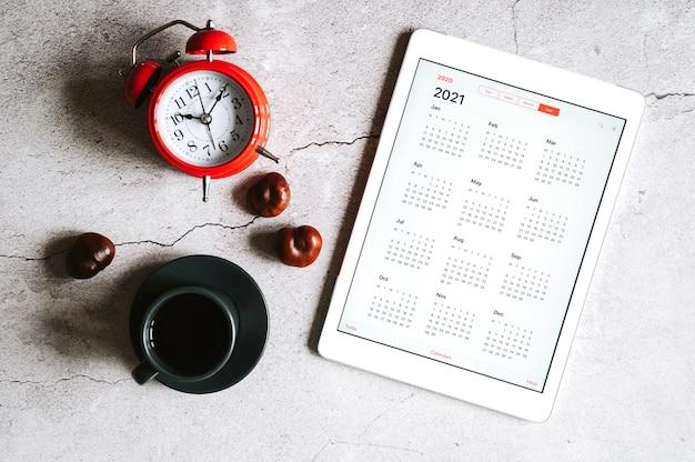 Um tablet com calendário aberto para 2021 anos, uma xícara de café, castanhas e um despertador vermelho
