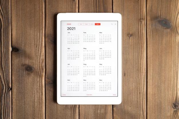 Um tablet com um calendário aberto para 2021 anos em um fundo de mesa de tábuas de madeira