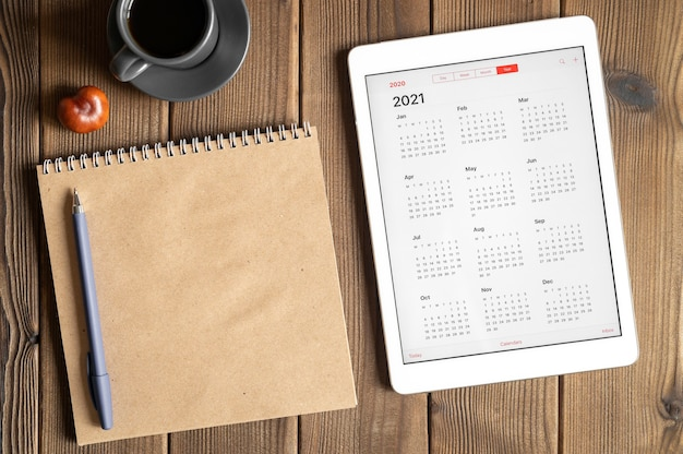 Um tablet com um calendário aberto para 2021 anos, uma xícara de café, castanhas e um caderno de papel artesanal em uma mesa de madeira